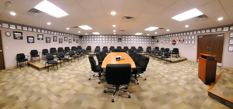 Wide-angle view of a room with a boardroom table in the center with additional chairs and framed awards along the walls.