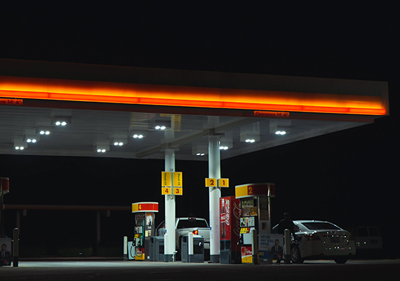 Nighttime view of a gas station, with two vehicles at the gas pumps.