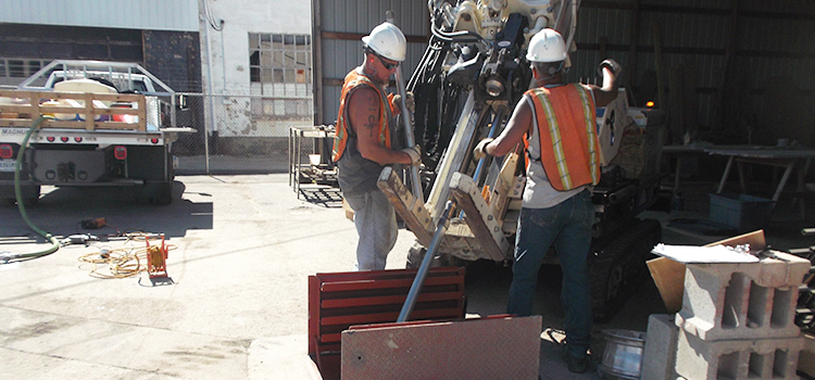 Two men direct a machine into an access panel in the ground.