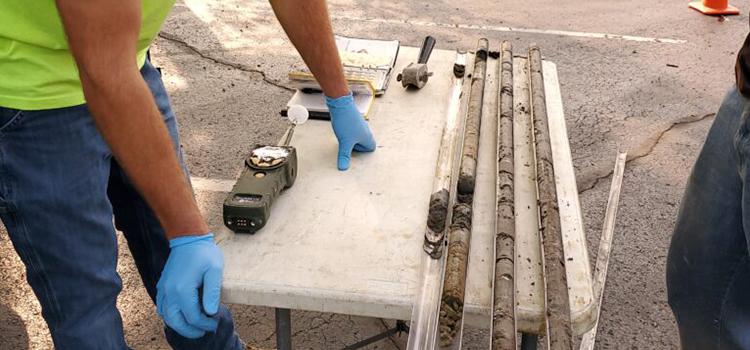 A Creek Run employee leans against a table, examining soil samples.