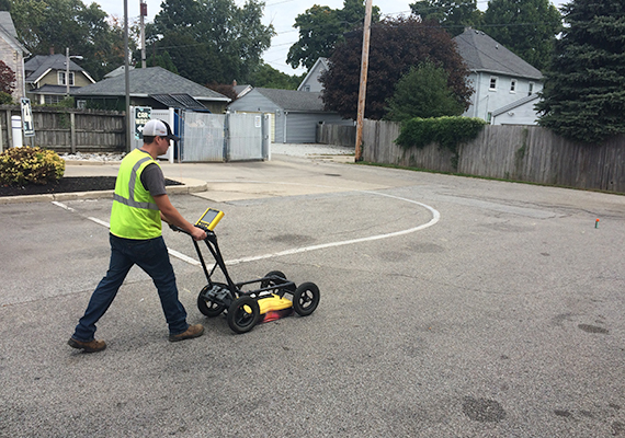 A Creek Run employee drives a Ground Penetrating Radar (which looks similar to a push mower) across a parking lot.