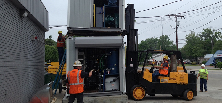 Multiple employees maneuver one remediation system to be stacked on another one.