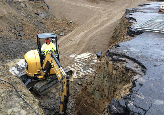 An employee operates an excavator in a pit of dirt and sand.