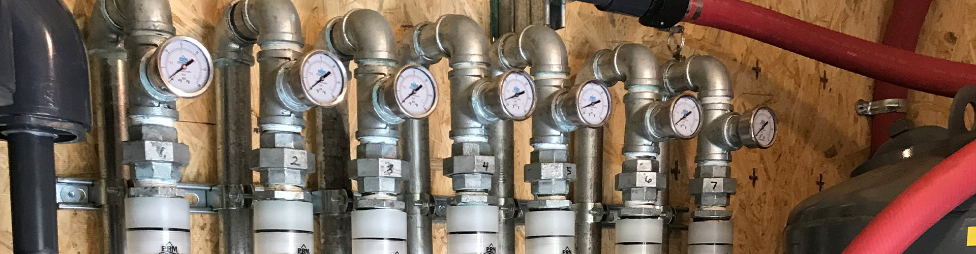External view of a remediation system build, specifically a row of silver pipes fitted with pressure gauges.