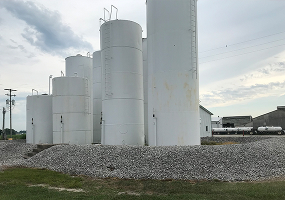 Multiple white silo-style tanks of various heights.