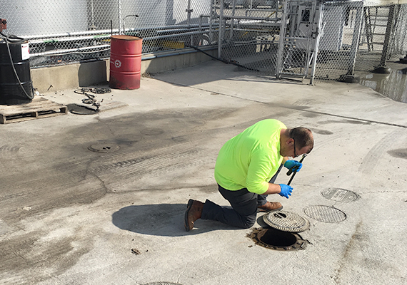 A man kneels on pavement and looks into an open maintenance access pipe with the manhole slid to one side.