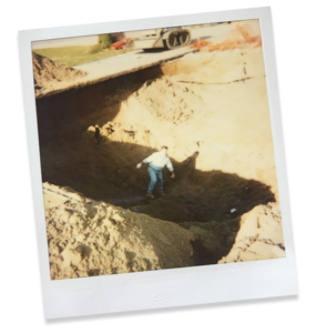 Vintage polaroid of a man standing in a deep hole of soil, with a small front loader in the background.